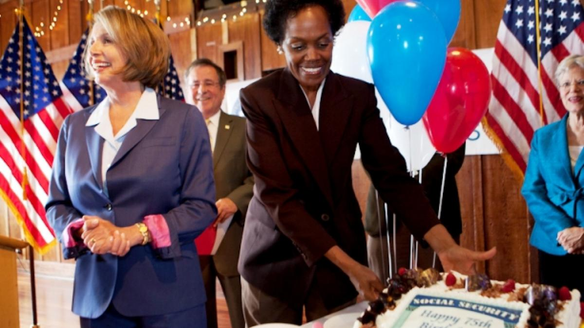 Congresswoman Pelosi standing at a table next to a cake