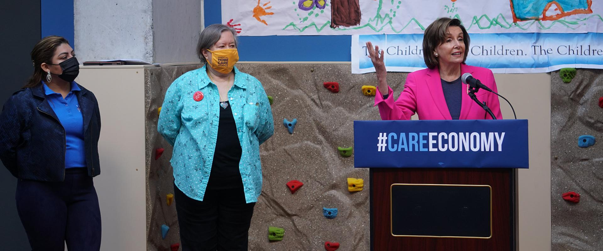 Pelosi speaking behind podium at Care Economy Week of Action
