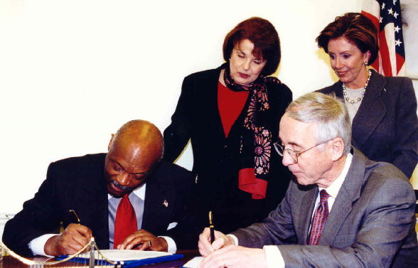 Nancy Pelosi and Senator Feinstein watch as Navy Secretary England and Mayor Brown sign an agreement for the cleanup and transfer of Hunters Point to San Francisco in January 2002